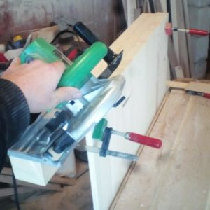 in order to cut the edge of the fir wood table top we clamped a prop on the panel edge