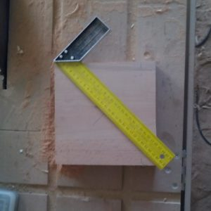 the 4 cm thick beech wood panel with the marks needed to drill the middle hole with a 30 mm drill