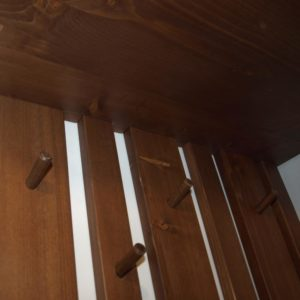 the wooden hooks, the different sizes of planks and the pine wood shelf are stained with walnut stain, are protected with water-base primer and are varnished with colorless water-based varnish