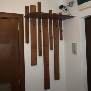 The appearance of the wooden wall mounted coat rack with different sizes of the planks and a shelf for storing the objects at the entrance hall of the apartment