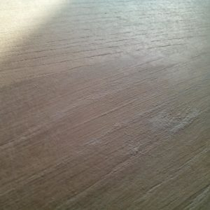 the small cracks of the oak wood planks are filled with the mix putty