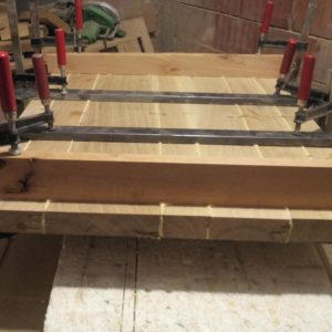 gluing the oak wood planks with polyurethane adhesive to build the thick tabletop