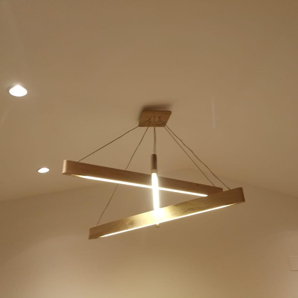 the decorative light fixture made out of solid oak wood with a special and modern design that also has a decorative role in a high room