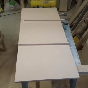 we cut two sticks from the raw MDF board which we will glue them on the edges of the base board of the painted MDF bathroom vanity cabinet