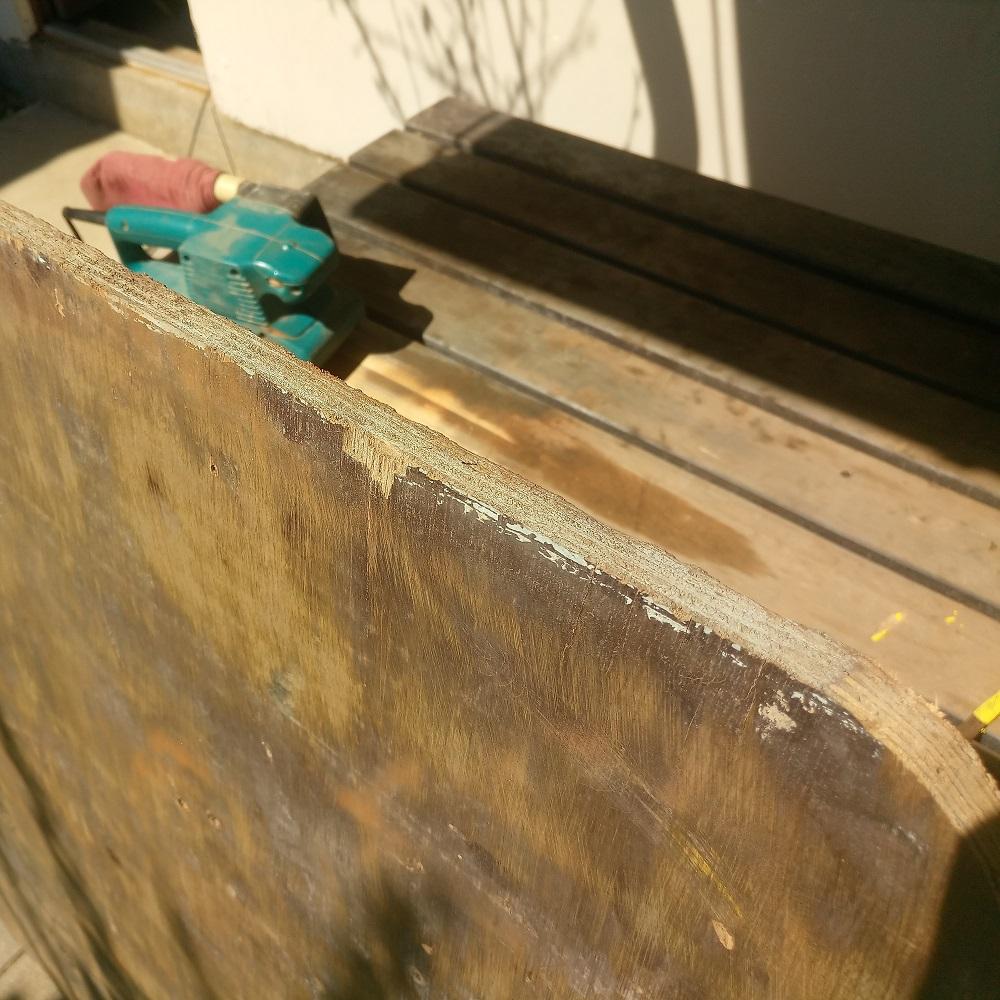 sanding the edges of the DIY basketball backboard using the belt sander