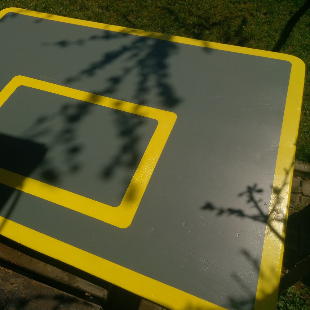 the backboard is painted in gray, with yellow lines