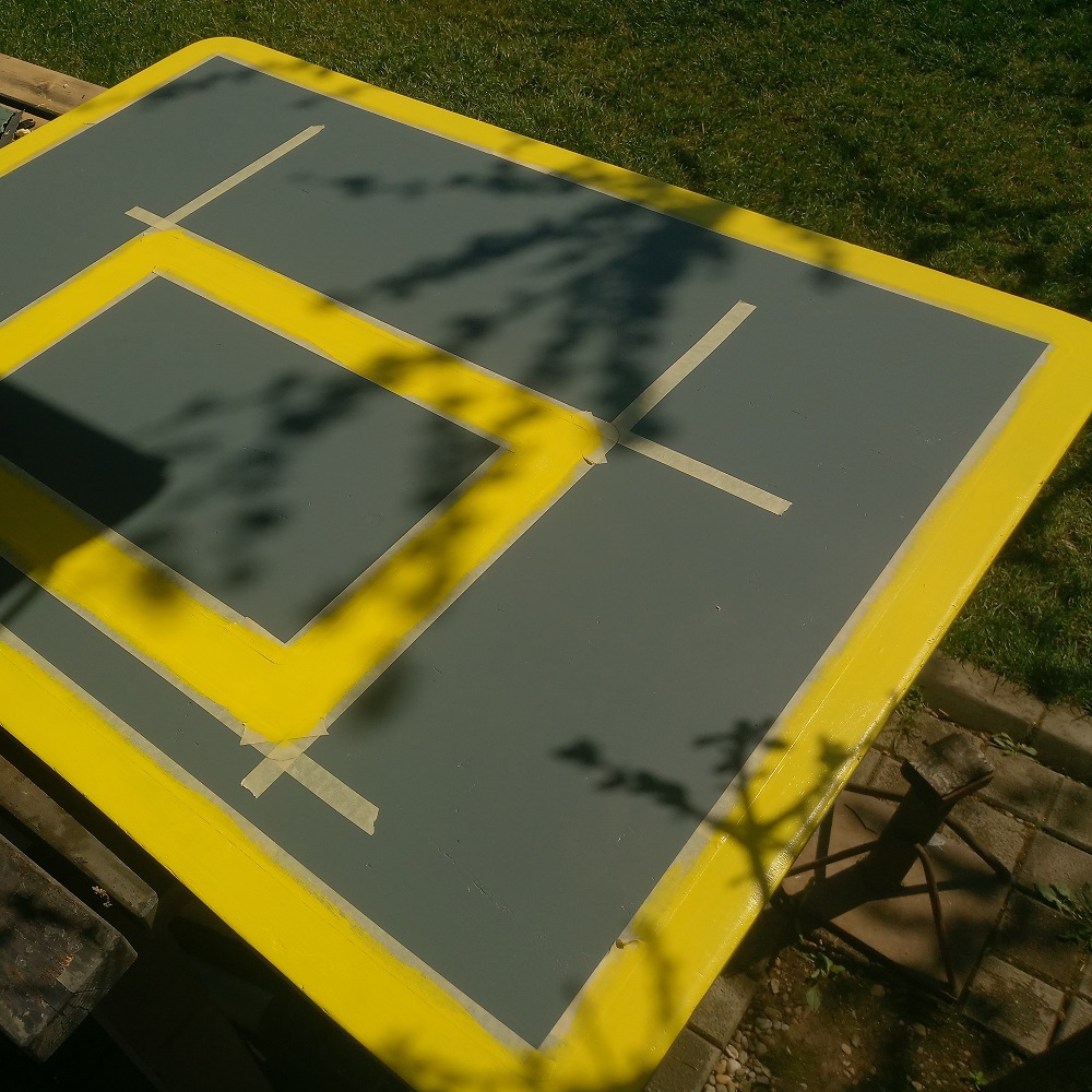 painting the yellow lines of the DIY basketball backboard