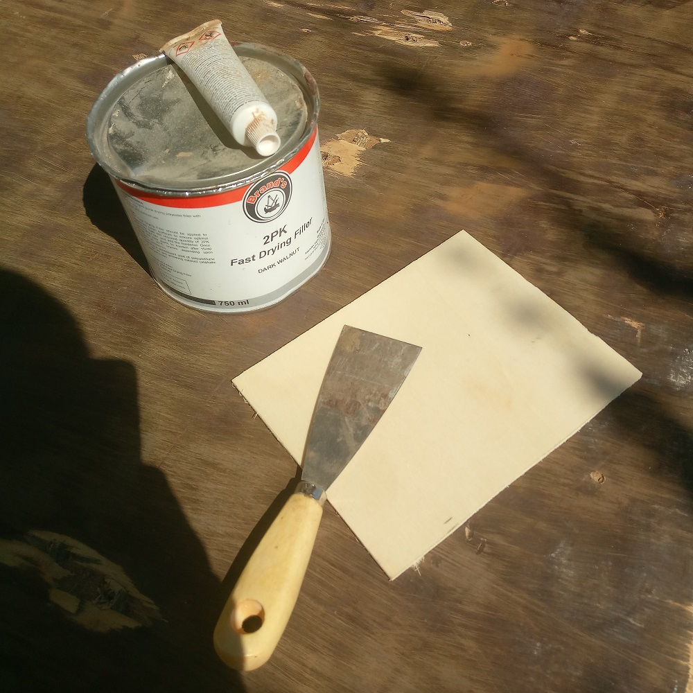 miximg the two part wood putty for filling the holes in the plywood panel