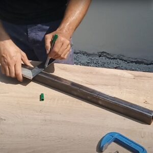 marking the positions of the cuts needed to be able to bend the square tube