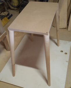 the four turned conical legs are screwed on the corners of the MDF board in order to be routed
