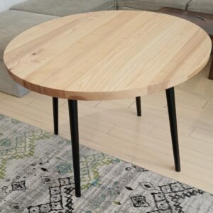 the round wooden kitchen table after we applied the polyurethane varnish and black paint