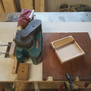 sanding the outside edges of the wooden decorative trays by using the band sander