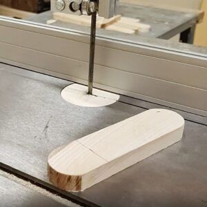 I drew a line on one of the small pieces used in the middle of the adjustable light, to cut it with the bandsaw