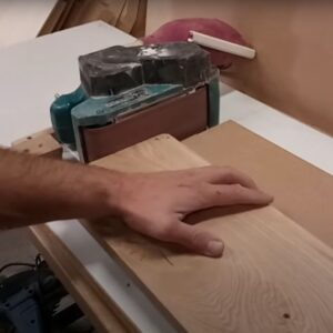 we round the corners of the wooden drawer fronts with the band sander secured on the workbench